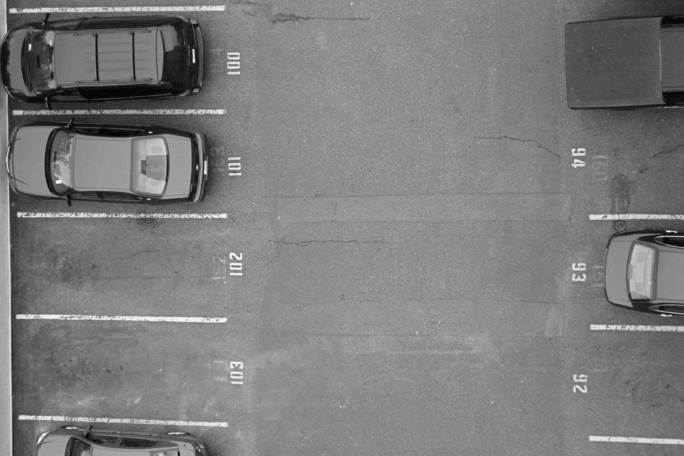 Black & White aerial photo of a parking lot with three cars to the left and two to the right.